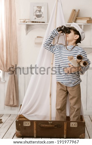 Little boy in the image of sailor playing in her room  - stock photo