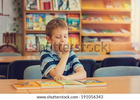 Little boy in the library - stock photo