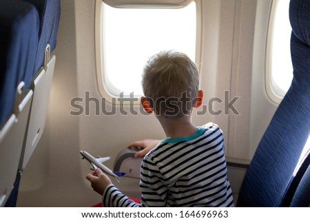 little boy in the plane looking out the window - stock photo