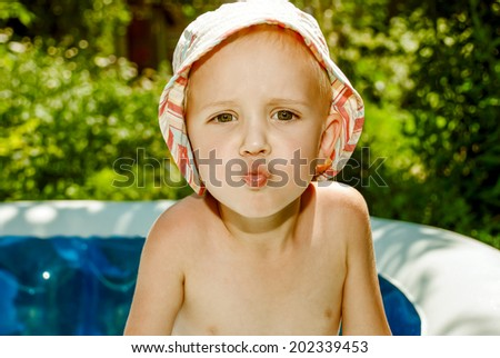 Little boy in the pool in Panama trying to kiss. - stock photo