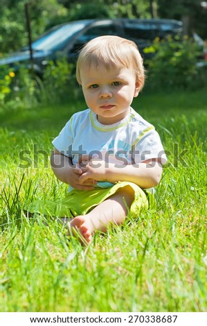 Little boy in the summer or spring park sitting on the grass in sunshine day - stock photo