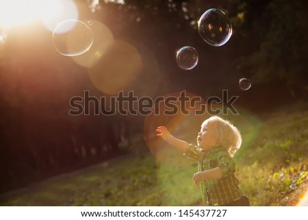 little boy in the sunset catches soap bubbles - stock photo