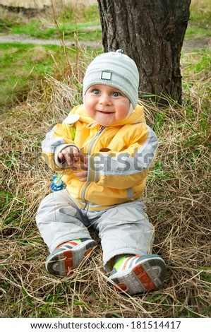 little boy in warm clothes sitting on the autumn grass - stock photo