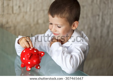 Little boy insert coin into piggy bank in office - stock photo