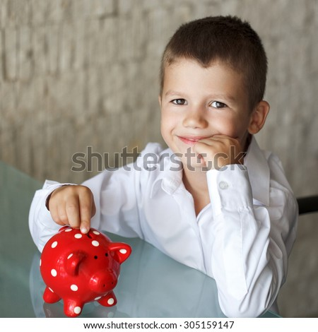 Little boy insert coin into red dotted piggy bank in office - stock photo