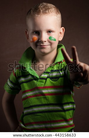 little boy is a fan of Ireland, a blond guy in a striped t-shirt, happy child posing for the camera - stock photo