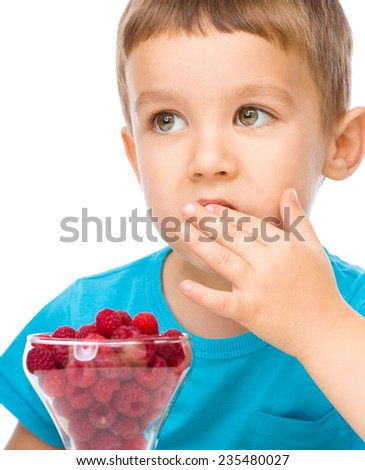 Little boy is eating raspberries, isolated over white - stock photo