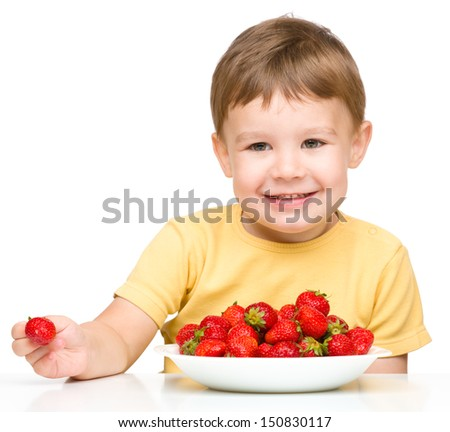Little boy is eating strawberries, isolated over white - stock photo