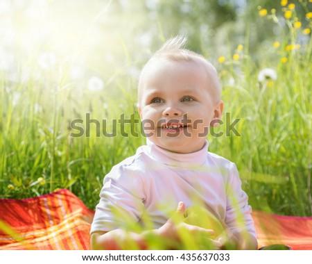 Little boy is happy sitting on the meadow - stock photo