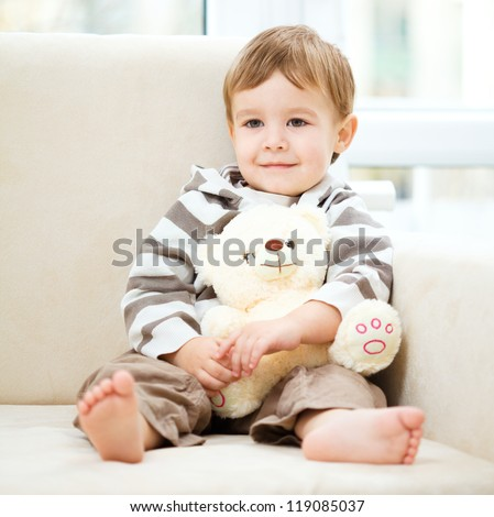Little boy is holding his teddy bear while sitting on a sofa - stock photo