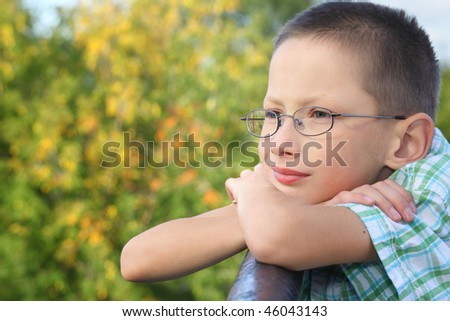 little boy is lean elbow on bridge fence and looking forward - stock photo