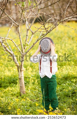 Little boy is playing hide-and-seek hiding face with hat. - stock photo