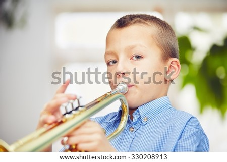 Little boy is playing the trumpet at home  - stock photo
