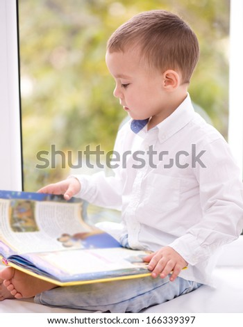 Little boy is reading book while sitting on windowsill, indoor shoot - stock photo