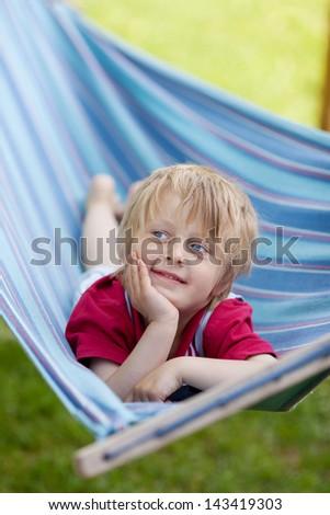 Little boy is relaxing in a hammock - stock photo