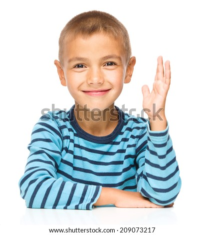 Little boy is rising his hand up, isolated over white - stock photo