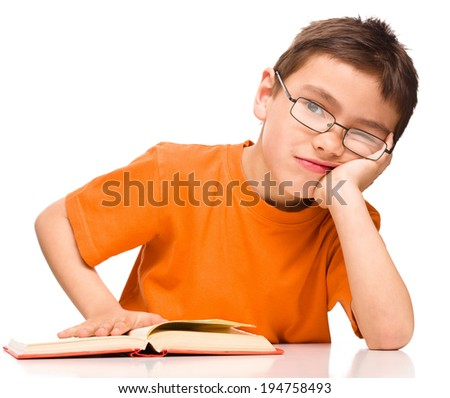 Little boy is tired to read his book, isolated over white - stock photo