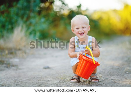Little boy iwith bucket n summer outdoor - stock photo