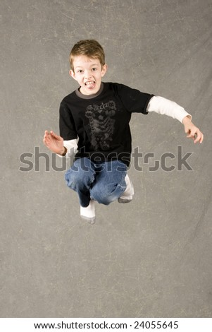 little boy jumping into air over gray background - stock photo