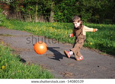 Little boy kicking a ball - stock photo