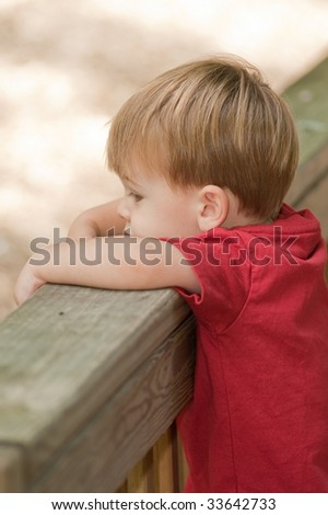little boy leaning over the deck railing - stock photo