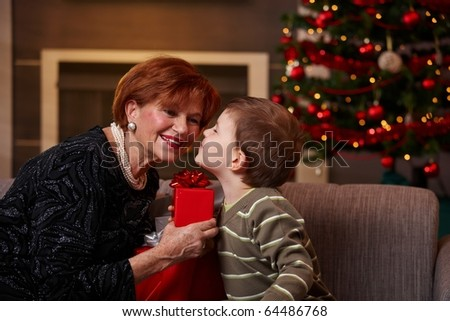 Little boy leaning to smiling grandmother with eyes closed, getting surprise christmas present. ? - stock photo