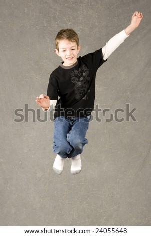 little boy leaping into air over gray background - stock photo