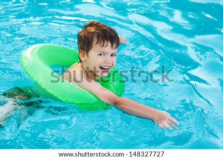 Little boy learning swim with saver in pool, teeth smile - stock photo