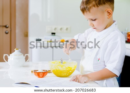Little boy learning to bake reading the recipe concentrating as he adds ingredients to the eggs in his mixing bowl - stock photo