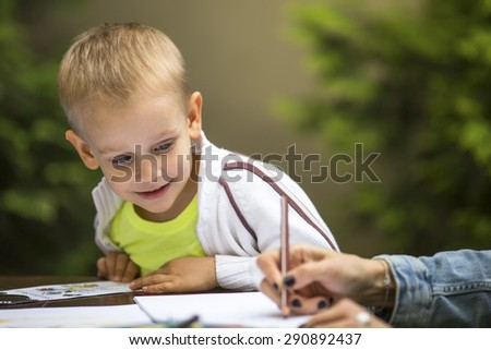 Little boy learning to draw with a pencil and with interest the hands of an adult. - stock photo