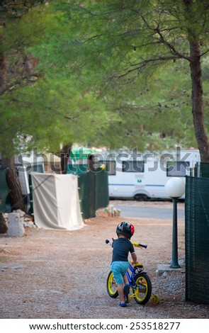 little boy learning to ride a bike in a campsite on holiday - stock photo