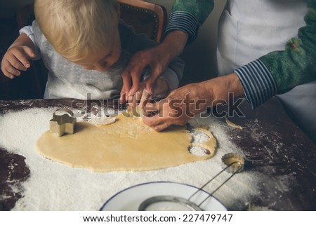 Little boy learns from her grandmother how to make Christmas cookies. - stock photo