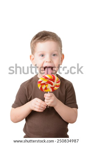 little boy licking a lollipop on a white background - stock photo