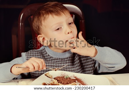 Little boy licking his fingers in appreciation of the tasty home baked slice of cake he is eating for dessert at the dining table - stock photo