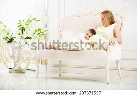 Little boy listening belly of his pregnant mother while lying on couch at home - stock photo