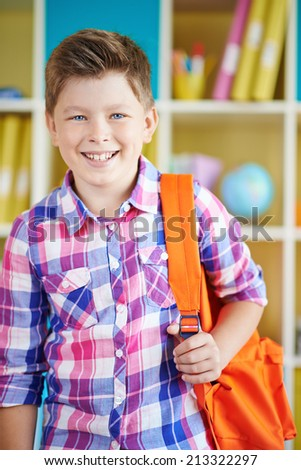Little boy looking at camera in school - stock photo