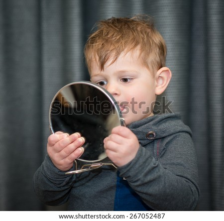 little boy looking at himself in a hand mirror - stock photo