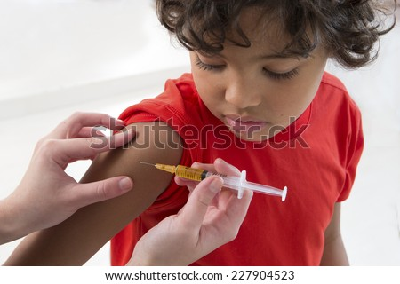 little boy looking at his arm, while receiving vaccine - stock photo