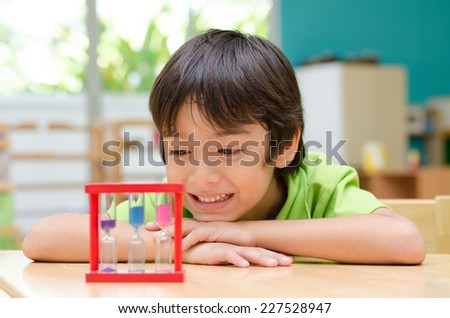 Little boy looking at hourglass in class - stock photo