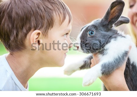 Little boy looking at pet rabbit in mom's hands - stock photo