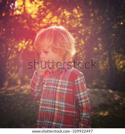 little boy looking at something while chewing on his fingers inside his mouth with a toned instagram filter with a red splash of color - stock photo