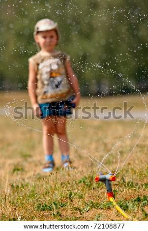 Little boy looking at watering sprinkler, focus on the sprinkler - stock photo