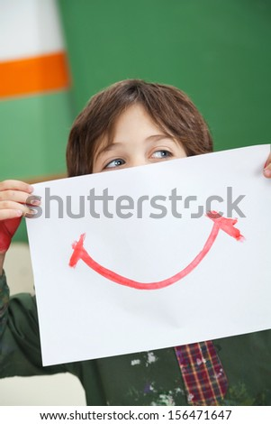 Little boy looking away while holding paper with smile drawn on it in front of face - stock photo
