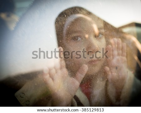 Little boy looking through window - stock photo