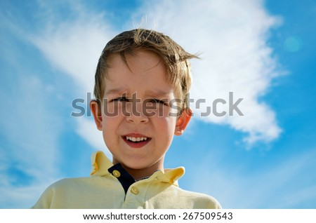 little boy looks down on blue cloudy sky background horizontal - stock photo