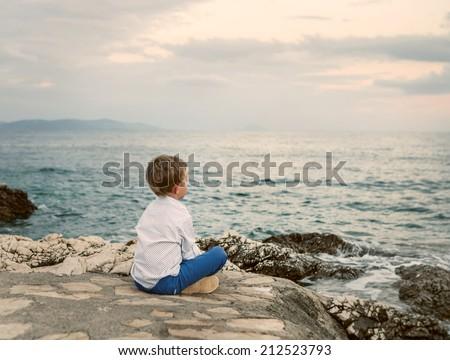 Little boy looks on the sunset sea landscape - stock photo