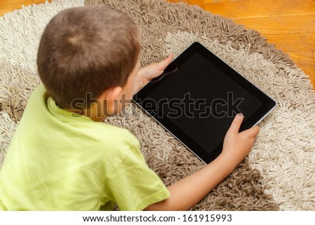 Little boy lying in the floor and looking at tablet  - stock photo