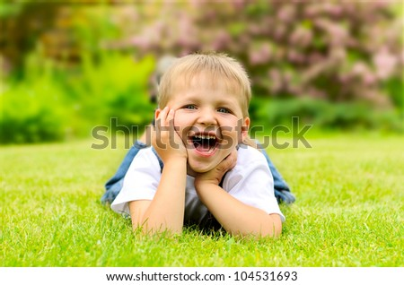 Little boy lying on a green grass - stock photo