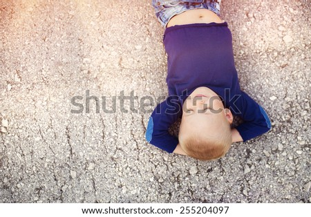 Little boy lying on the ground enjoying his time outside - stock photo