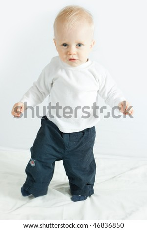 little boy making his first steps - on white - stock photo